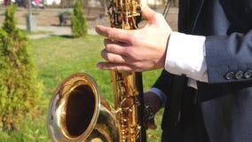 Um homem executa os azuis em um saxofone em um parque da cidade homem que joga a música jazz do saxofone Saxofonista no revestime video estoque