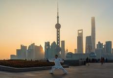 Um homem exercita e faz Tai Chi na barreira enquanto o sol aumenta imagem de stock