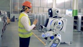 Um homem fala ao robô em uma fábrica