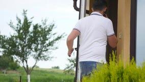 Um homem fala o telefone e pela vinda em casa video estoque