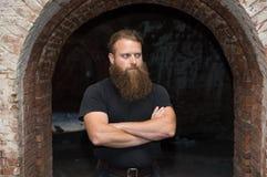 Um homem farpado com os braços cruzados, suportes em uma sala sombrio sob um arco curvado fotografia de stock royalty free