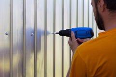 Um homem farpado com uma chave de fenda parafusou à disposição o perfil do metal de folhas dos parafusos Foto de Stock Royalty Free