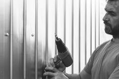 Um homem farpado com uma chave de fenda parafusou à disposição o perfil do metal de folhas dos parafusos Imagens de Stock Royalty Free