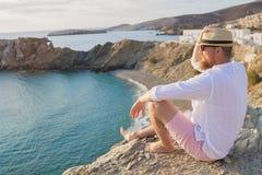 Um homem farpado do moderno em férias senta-se em um litoral íngreme e olha-se na distância foto de stock royalty free