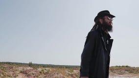 Um homem farpado em um casaco preto no deserto que procura alguém vídeos de arquivo