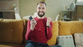 Um homem farpado feliz está fazendo um negócio ou uma vitória bem sucedida com telefone e exulta-os em casa Freelancer ou homem d filme