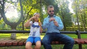 Um homem farpado funde bolhas de sabão junto com sua filha T video estoque