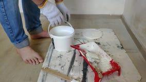 Um homem farpado grisalho mistura a pintura branca em uma cubeta por uma vara e derrama-a no recipiente vídeos de arquivo