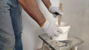 Um homem farpado grisalho mistura a pintura branca em uma cubeta por uma vara e derrama-a no recipiente video estoque