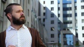 Um homem farpado nos vidros olha mindfully à esquerda e alisa sua barba Decola seus vidros que olha fixamente na distância T video estoque
