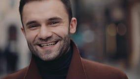 Um homem farpado novo atrativo no equipamento ocasional que sorri felizmente para a câmera Beleza masculina Vida urbana, ativa vídeos de arquivo
