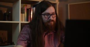 Um homem farpado novo com vidros é surpreendido muito trabalhar no computador filme