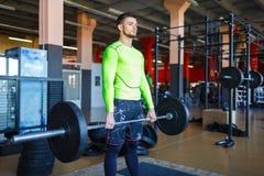 Um homem farpado novo está treinando com um barbell no gym imagens de stock