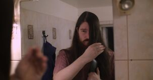 Um homem farpado novo que penteia seu cabelo longo video estoque