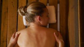 Um homem faz uma massagem da parte traseira e do pescoço mulher bonita na sauna, banho video estoque