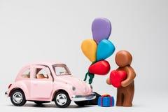 Um homem feito do plasticine ao lado de um carro com os balões no fundo branco, alinhado no centro foto de stock