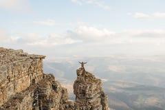 Um homem feliz com suas mãos acima da elevação está sobre uma rocha separadamente estando que esteja acima das nuvens contra Foto de Stock