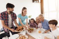 Um homem feliz dá um peru a uma tabela festiva para a ação de graças Fotografia de Stock Royalty Free