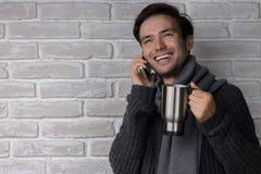 Um homem feliz que fala no telefone e que bebe uma bebida de aquecimento Imagem de Stock Royalty Free