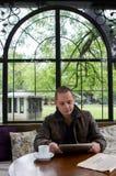 Um homem feliz que lê um ebook em uma cafetaria fotografia de stock royalty free