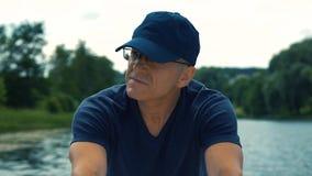 Um homem fino, sério, grisalho nos vidros, um tampão azul e um t-shirt azul que enfileiram um barco branco no rio em um verão filme