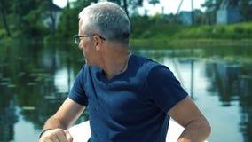 Um homem fino, sério, grisalho nos vidros, um tampão azul e um t-shirt azul que enfileiram um barco branco no rio em um verão vídeos de arquivo