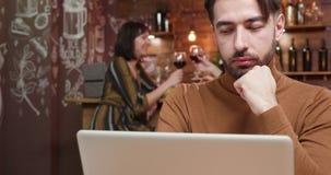 Um homem focalizado que lê um texto de sua tela do portátil filme