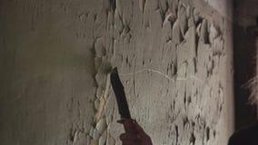 Um homem fresco em uma capa de chuva preta e em um chapéu entra um corredor escuro em uma construção abandonada e gasta-o no movi vídeos de arquivo