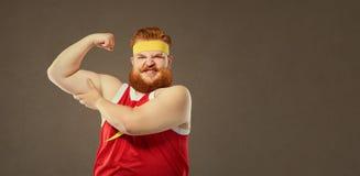 Um homem gordo em um terno do esporte mantém seus músculos em seu braço fotos de stock royalty free