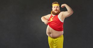 Um homem gordo engraçado com uma barriga grande mostra os músculos em seu braço imagens de stock