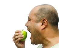 Um homem gordo está forçando-se para comer uma maçã Fotografia de Stock