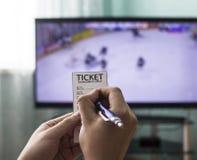 Um homem guarda um bilhete do editor e aposta-o em esportes, na tevê vai hóquei, close-up fotos de stock