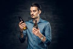 Um homem guarda duas cervejas engarrafadas ofício fotos de stock