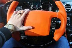 Um homem guarda o volante de um carro luxuoso Relógio de ouro e um anel em sua mão fotos de stock royalty free