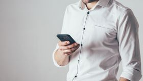 Um homem guarda um telefone em sua mão no fundo branco É vestido em uma camisa branca com inserções pretas e nos olhares contínuo imagem de stock