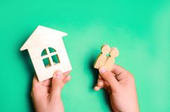 Um homem guarda uma família e uma casa em suas mãos Conceito de bens imobiliários comprando, aluguer, vendendo uma casa hipoteca, imagem de stock royalty free