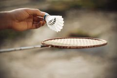 Um homem guarda uma peteca branca e uma raquete de badminton fotos de stock royalty free
