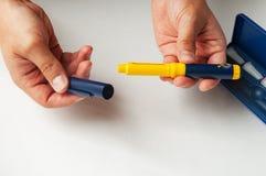 Um homem guarda uma seringa para a injeção subcutâneo de drogas hormonais na fecundação do protocolo de IVF in vitro Imagens de Stock