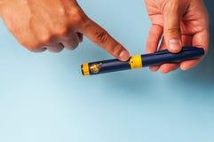 Um homem guarda uma seringa para a injeção subcutâneo de drogas hormonais na fecundação do protocolo de IVF in vitro Foto de Stock Royalty Free