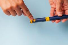 Um homem guarda uma seringa para a injeção subcutâneo de drogas hormonais na fecundação do protocolo de IVF in vitro Fotografia de Stock Royalty Free