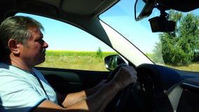 Um homem idoso aprecia viajar e conduz um carro na alta velocidade vídeos de arquivo