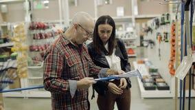 Um homem idoso com filha adulta em um supermercado do hardware escolhe o ancinho filme