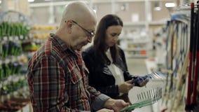 Um homem idoso com a filha adulta nas prateleiras do negócio do supermercado escolhe um ancinho de jardim filme