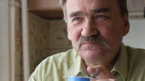Um homem idoso com um bigode guarda um copo da bebida quente e bebe-o Senta-se perto da janela e tem-se o café da manhã em casa vídeos de arquivo