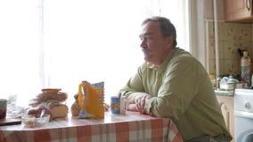 Um homem idoso com um bigode guarda um copo da bebida quente e bebe-o Senta-se perto da janela e tem-se o café da manhã em casa video estoque