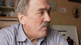 Um homem idoso com um bigode guarda um copo da bebida quente e bebe-o Senta-se perto da janela e tem-se o café da manhã em casa filme