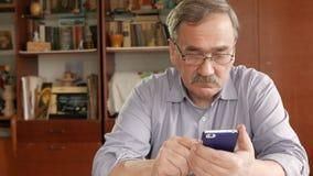 Um homem idoso com um bigode nos vidros disca uma mensagem de texto em seu telefone celular Senta-se em casa na tabela vídeos de arquivo