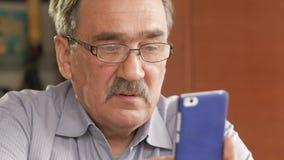 Um homem idoso com um bigode nos vidros disca uma mensagem de texto em seu telefone celular Senta-se em casa na tabela video estoque