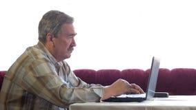 Um homem idoso com um bigode senta-se atrás de um portátil e resolve-se problemas Olha seriamente no monitor filme