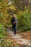 Um homem idoso corre ao longo do trajeto na floresta Fotografia de Stock